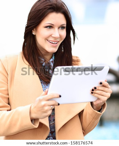 Businesswoman in coat working on digital tablet out of office overlooking cityscape - stock photo