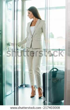 Businesswoman in elevator. Full length of beautiful young businesswoman in formalwear pushing button while standing inside of elevator - stock photo