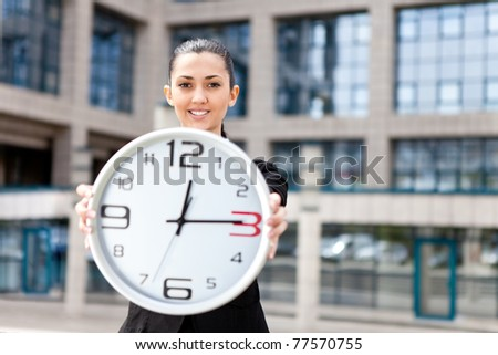 businesswoman in front her office building showing time