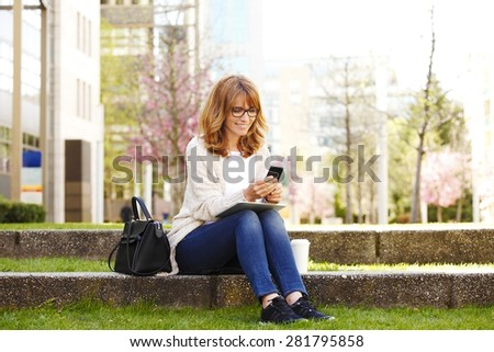 Businesswoman in front of an office building have a break.Typing message on smart phone and using her digital tablet.  - stock photo