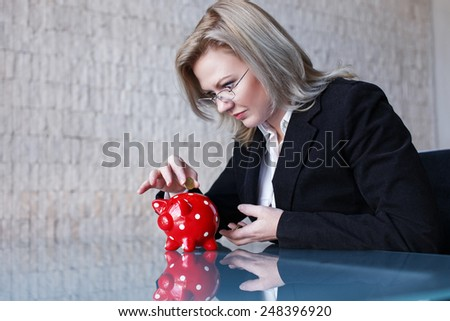 Businesswoman in glasses put coins into red dotted piggy bank, saving - stock photo