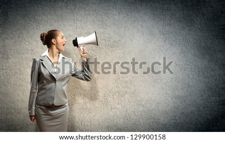 businesswoman in grey suit screaming into megaphone - stock photo