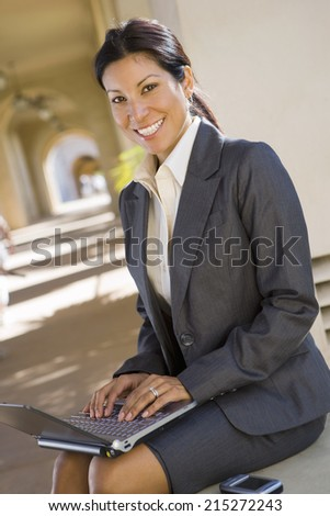 Businesswoman, in grey suit, using laptop in building arcade, smiling, side view, portrait (tilt)