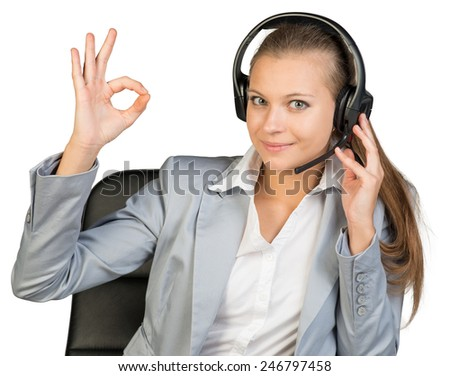 Businesswoman in headset making okay gesture, her other hand on headset speaker, looking at camera, smiling. Isolated over white background - stock photo