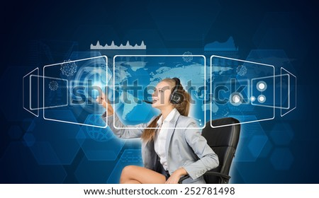 Businesswoman in headset sitting on chair using touch screen interfaces, smiling, on blue technology background - stock photo