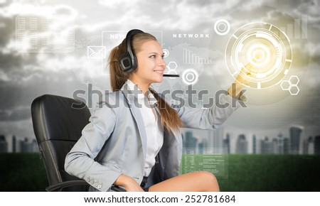 Businesswoman in headset sitting on chair using virtual interface. City, world map and graphs over cloudy sky as backdrop