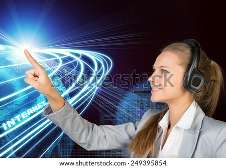 Businesswoman in headset touching spot of light with rays around, smiling. Beside is Globe surrounded by light streams of communication. Wire-frame building as backdrop - stock photo