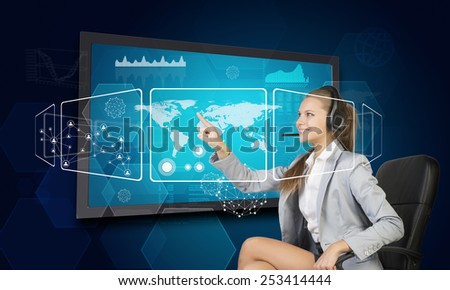 Businesswoman in headset using touch screen interface with world map, graphs and other elements, on blue background