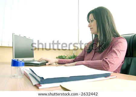 Businesswoman in her office working on laptop