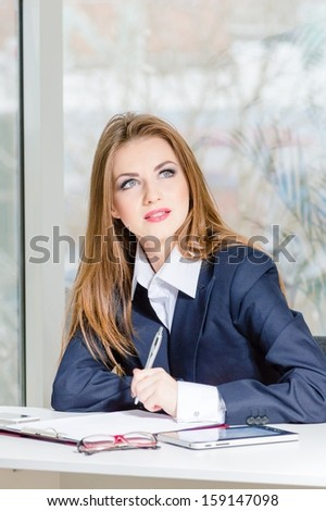 Businesswoman in man's suit signing with pen at her office fashion styled looking up