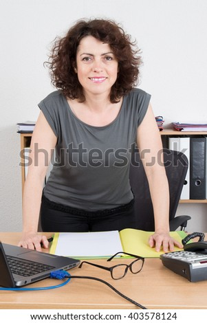 Businesswoman in meeting room writing on folders