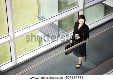 Businesswoman in modern office building, arriving for work - stock photo