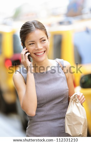 Businesswoman in New York talking on the phone walking busy with lunch break doggie bag smiling happy. Young beautiful multiracial Caucasian / Chinese Asian business woman. - stock photo