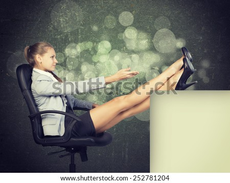 Businesswoman in office chair, looking at camera, with her feet up on anything, in front of scratched wall with sketch of city