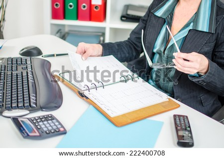 Businesswoman in office checking her diary - stock photo