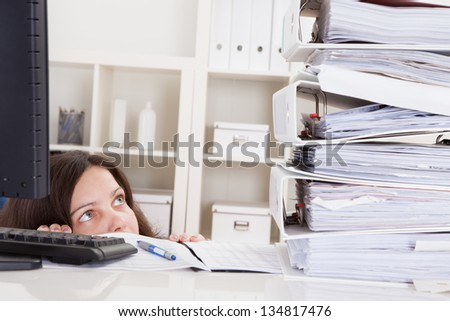 Businesswoman In Office Looking At Stack Of Folders