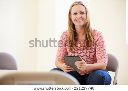 Businesswoman In Office Using Digital Tablet - stock photo