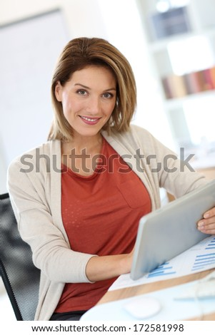 Businesswoman in office working on digital tablet - stock photo