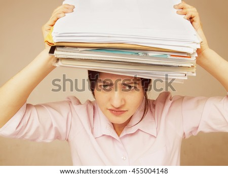 Businesswoman in problems. Alone working in office with a lot of documents. (psychological portrait, aggression, anger, frustration) - stock photo
