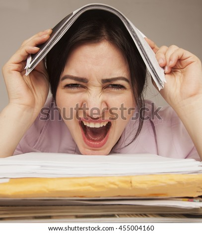 Businesswoman in problems. Alone working in office with a lot of documents. Yelling and screaming for bad results. (psychological portrait, aggression, anger, frustration) - stock photo