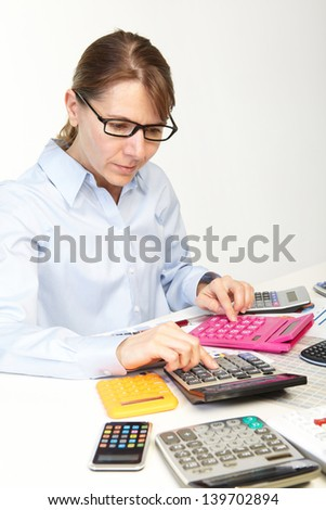 Businesswoman in spectacles sits at office near calculators