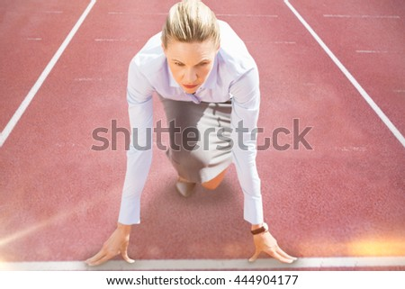 Businesswoman in starting blocks against race track
