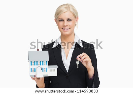 Businesswoman in suit holding a model house against white background