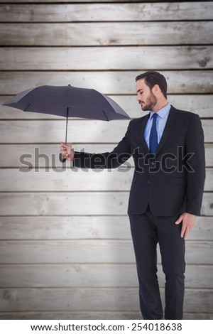 Businesswoman in suit holding umbrella against wooden planks - stock photo