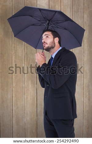 Businesswoman in suit holding umbrella while looking up against wooden surface with planks - stock photo