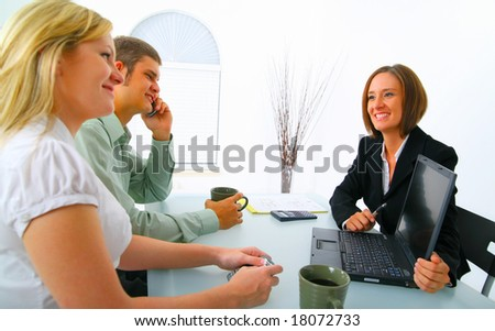 businesswoman in suit showing laptop to professional young couple. concept for purchasing property, car, or investment - stock photo