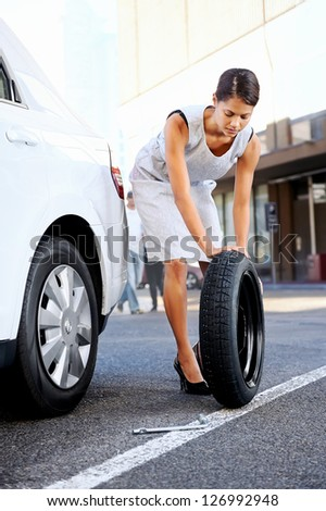 businesswoman in the city with flat tire frustrated - stock photo