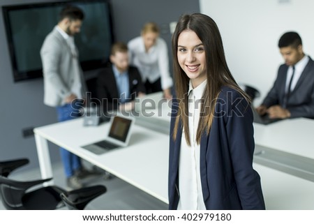 Businesswoman in the office with her colleagues behind - stock photo