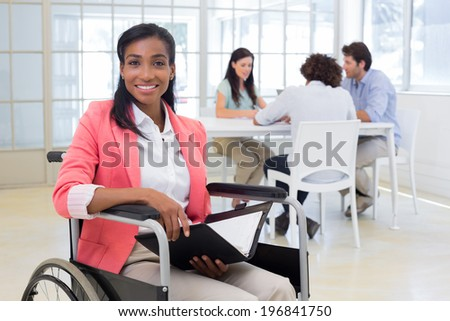Businesswoman in wheelchair holding folder and smiling at camera in the office - stock photo