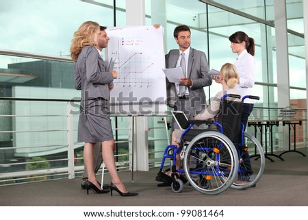 Businesswoman in wheelchair with colleagues - stock photo