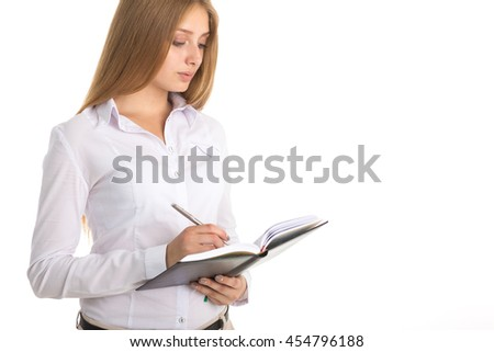 Businesswoman in white shirt takes notes in a notebook
