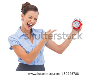 Businesswoman indicating alarm clock with finger
