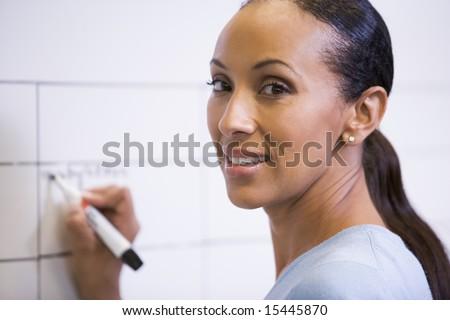 Businesswoman indoors writing on erasable board - stock photo