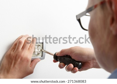 Businesswoman installing a silver light switch with a screwdriver on a white wall, repairing an electrical problem by herself. Do-it-yourself (DIY) and emancipation concept.