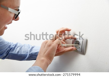 Businesswoman installing a silver wall-mounted AC power socket with a screwdriver on a white wall, repairing an electrical problem by herself. Do-it-yourself (DIY) and emancipation concept. 