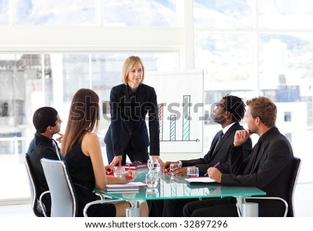Businesswoman interacting to her team in a meeting - stock photo