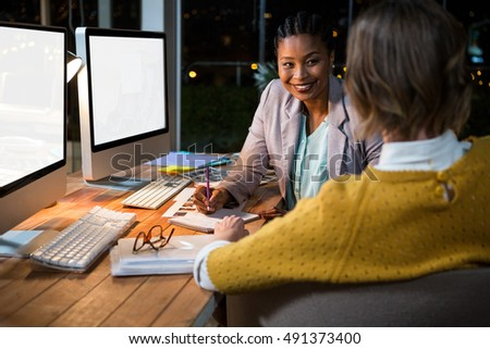 Businesswoman interacting with colleague in the office