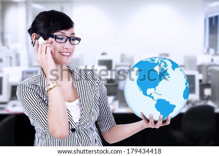 Businesswoman is calling and holding a blue world global at office - stock photo