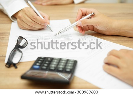 Businesswoman is explaining terms and conditions in agreement to his client before he sign the document - stock photo