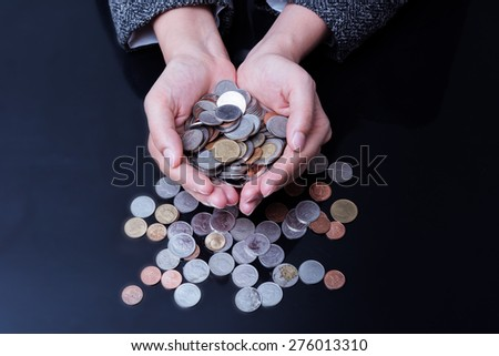 Businesswoman is having hands full of coins. Business profit concept.