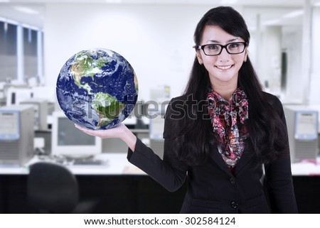 Businesswoman is holding world globe at office - stock photo