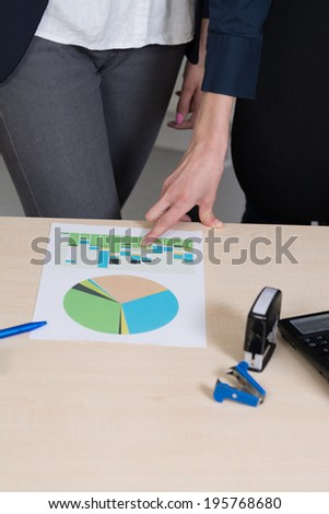 Businesswoman is pointing to a document with her finger. Another woman is standing besides her. - stock photo
