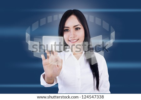 Businesswoman is pressing virtual icons on blue background - stock photo