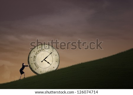 Businesswoman is pushing a big time clock on top of a hill. The clock is written Time - stock photo