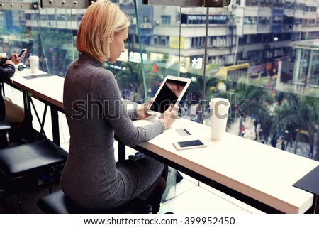 Businesswoman is reading world news on touch pad with copy space screen for your advertising text message or content. Young female is watching video on digital tablet during rest in modern coffee shop - stock photo