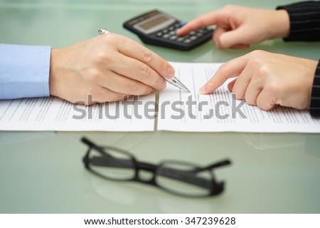 businesswoman is reviewing document with tax consultant and making calculations to optimize report - stock photo